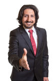 Turkish businessman reaching his hand and says hello. Standing turkish businessman with beard, dark suit and tie reaching his hand and says hello on an isolated stock photography