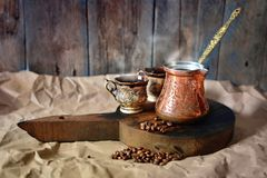 Turkish coffee background with copper coffee pot, cups and coffee beans on a wooden desk.  stock images