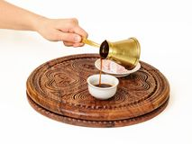 Turkish coffee is being poured into Turkish coffee cup. She is serving a black coffee from Turkish coffee pot a jazve or an ibrik, and pouring it in Turkish royalty free stock photo
