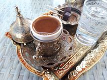 Turkish coffee and chocolate delight on copper tray. Turkish coffee in ottoman style ornamental cup with water glass Royalty Free Stock Photography