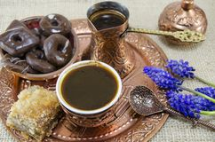 Turkish coffee with cookies and flowers. In copper cups on a plate Royalty Free Stock Photo