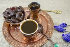 Turkish coffee with cookies and flowers. In copper cups on a plate Stock Images