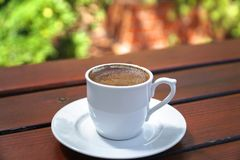 Turkish Coffee Cup on a Wooden Table. Turkish Coffee Cup with bubbles on a Wooden Table Royalty Free Stock Photos