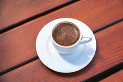 Turkish Coffee Cup on a Wooden Table. Turkish Coffee Cup with bubbles on a Wooden Table Royalty Free Stock Photo