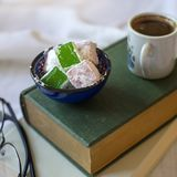 Turkish coffee with Turkish delight  resting on two books Stock Photo