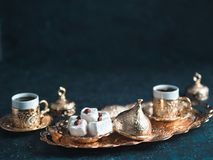 Turkish delight and turkish coffee. Turkish coffee with delight and traditional copper serving set on dark background. Assorted traditional turkish dilight or royalty free stock photography