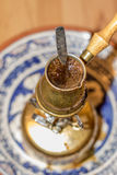 Turkish coffee pot boiling on portable stove. Royalty Free Stock Images