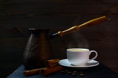 Turkish coffee pot. Closeup of a copper coffee pot for making Turkish coffee, a cup of hot coffee and cinnamon on a wooden table at dark background Stock Photo