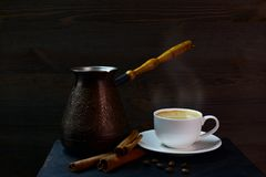 Turkish coffee pot. Closeup of a copper coffee pot for making Turkish coffee, a cup of hot coffee and cinnamon on a wooden table at dark background Stock Photos