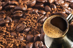 Turkish coffee-pot over coffee background. Turkish coffee-pot over coffee-beans and instant coffee background Stock Image