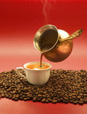 Turkish coffee is poured from a copper pot. On a red background coffee beans Stock Photos