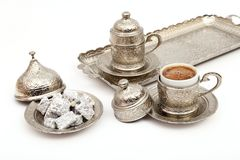 Turkish coffee in traditional silver cup with Turkish delight on isolated white background.  royalty free stock images