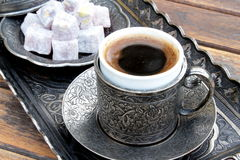 Turkish coffee and turkish delight. With old traditional embossed metal cup stock photos