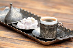 Turkish coffee and turkish delight. With old traditional embossed metal cup royalty free stock photography