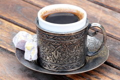 Turkish coffee and turkish delight. With old traditional embossed metal cup stock photography