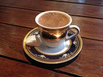Turkish coffee with Turkish delight at a café. Turkish coffee served in a small, pretty cup and saucer with a side of Turkish delight, shot on a wood-slat table Stock Image