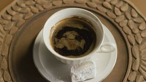 Turkish coffee with Turkish delight in rotation. Traditional dessert and black cafe in porcelain cup on wooden plate. Concept of tradition stock video