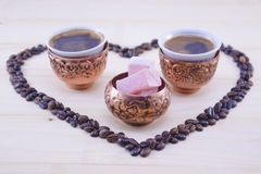 Turkish coffee and Turkish delight on a table. Turkish coffee and Turkish delight in a cofee beans shaped heart Stock Image