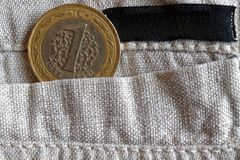 Turkish coin with a denomination of 1 lira in the pocket of old linen pants with empty black stripe for label. Turkish coin with a denomination of one lira in Royalty Free Stock Image