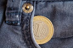Turkish coin with a denomination of one lira in the pocket of obsolete blue denim jeans. Turkish coin with a denomination of 1 lira in the pocket of obsolete Stock Photo