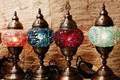 Traditional Turkish mosaic lamps for sale. Turkish colourful vintage lamps made of coloured glass mosaic and metal. Lamps standing on wall background royalty free stock photo