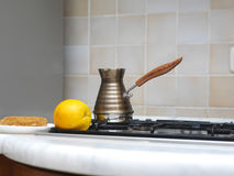 Turkish Copper Coffee Pot. Copper turkish coffee pot on a stove top next to a lemon and brownie Stock Photo