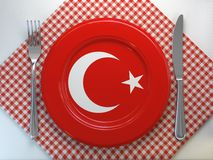 Turkish cuisine or turkish restaurant concept. Plate with flag ofTurkey with knife and fork royalty free stock photo