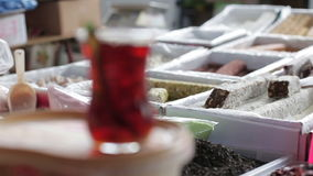 Turkish cup of hot tea is on the counter at the market. In the background tea and Turkish sweets Eastern stock footage