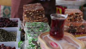 Turkish cup of hot tea is on the counter at the market. In the background tea and Turkish sweets Eastern stock video