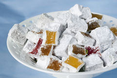Turkish Delight. Delicious Turkish delight, some cut, ready to eat, in a white bowl over blue background royalty free stock photo