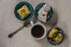 Turkish delight baklava and tea. Turkish delight, baklava and tea on the table in ethnic dishes stock images