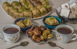 Turkish delight baklava and tea. Turkish delight, baklava and tea on the table in ethnic dishes stock photography