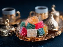 Turkish delight and turkish coffee. Turkish coffee with delight and traditional copper serving set on dark background. Assorted traditional turkish dilight or stock photo