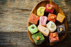 Turkish delight. On a dark wood background. toning. selective focus on the middle of plate stock image