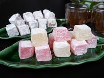 Turkish delight with fruit aroma. Turkish delight on a green leaf shaped tray, on dark brown background royalty free stock image