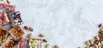 Turkish delight, pistachio and small dry roses. Mixture of oriental sweets rahat lukum, pistachios and small roses on a white concrete background. View from the Stock Photography