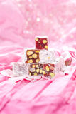 Turkish delight with pistachios nut. In glitter pink and rose petals stock photos