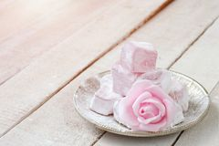 Turkish delight with rose flavor. In metal plate, pink rose flower on wooden table, closeup royalty free stock photography