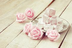 Turkish delight with rose flavor. In metal plate, pink roses flowers on wooden table royalty free stock image