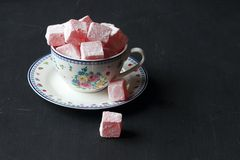 Turkish delight with tose flavoured ,Lokum. Turkish delight with rose flavoured ,Lokum in a cup on a black background royalty free stock photos