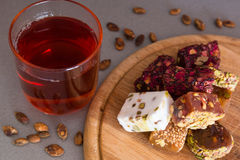 Turkish delight with tea on a wooden background Royalty Free Stock Photos