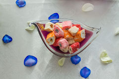 Turkish delight in vase. Colorful turkish delight in vase with blue and white rose petals on white tableclothe Stock Image