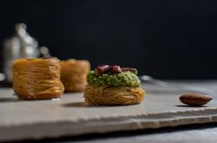 Middle Eastern dessert with pistachio called mabroume or burma isolated on blue background stock image