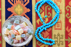 Turkish delights and blue rosary on traditional turkish carpet Royalty Free Stock Photos