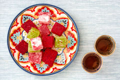 Turkish delights and tea on blue background Stock Photos