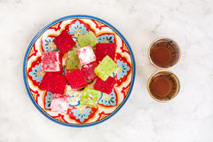 Turkish delights and tea on marble background Royalty Free Stock Photo