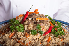 Turkish dish with pilaf in the hands of the cook Stock Images
