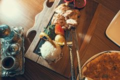Turkish dish with rise. Chiken, sause, pizza and coffee in silver cup holder on the restaurant table stock images
