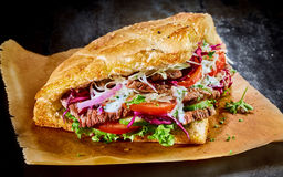 Turkish doner kebab on golden toasted pita bread. Filled with rotisserie roasted meat and fresh salad ingredients served on brown paper royalty free stock image
