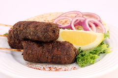 Turkish donner kofte kebab with salad. A traditional turkish donner kofte kebab with a lettuce, onion, lemon garnish served with pita bread Royalty Free Stock Photography